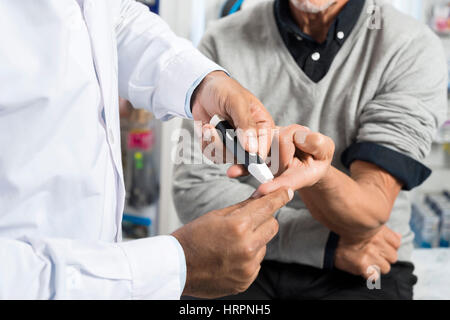 Midsection of male doctor checking sugar level of senior patient with glucometer in pharmacy - Stock Photo