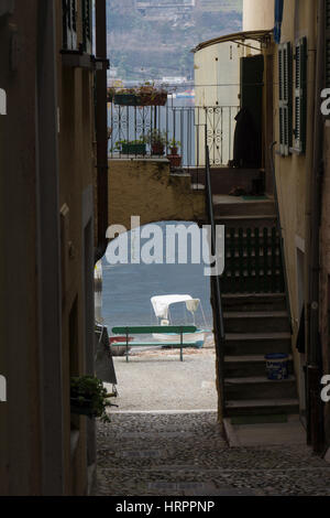 Small boat on a shore seen through a narrow street with archway on Isola dei Pescatori, Isola Superiore in lago - Stock Photo