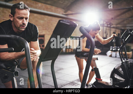 Young man and woman in sportive outfit taking rest and breathing deep after riding on cycling machines. - Stock Photo