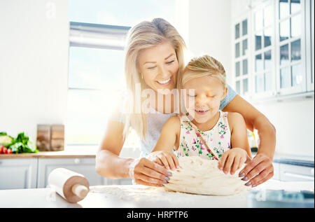 Pretty little girl kneading dough with her mother laughing with joy as she learns to bake, close up view with bright - Stock Photo