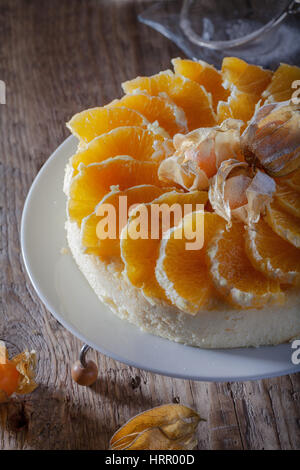 Cheesecake decorated with oranges and physalis on a - Stock Photo
