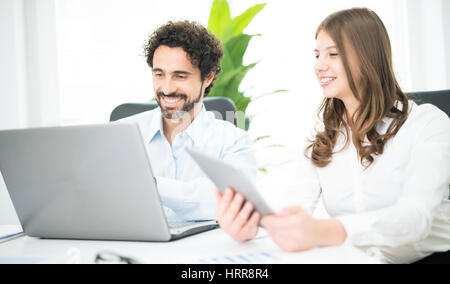 Business people at work in their office. Focus on the man - Stock Photo