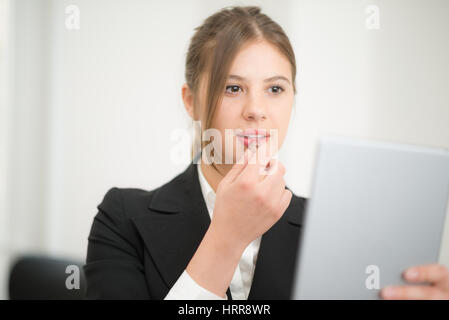 Woman using her tablet as a mirror to put on some lipstick in the office - Stock Photo