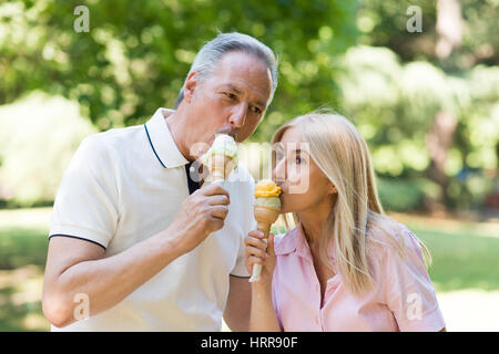 Portrait of an happy mature couple eating an ice cream in a park - Stock Photo