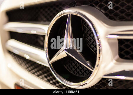 ABU DHABI, UAE - NOV 26, 2016: Mercedes Benz company logo on a car illuminated at night - Stock Photo