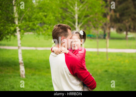 Closeup portrait of happy family. Little funny girl of 4 years age playing outside with her parents in spring city - Stock Photo