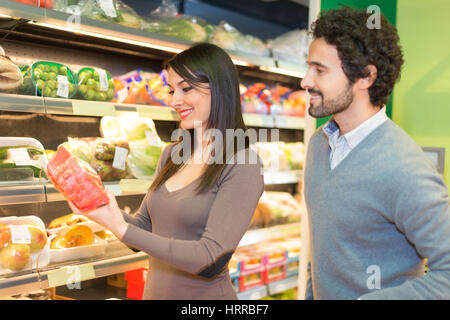 Couple shopping in a supermarket. The woman is reading a label - Stock Photo