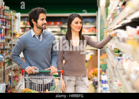 Young couple choosing the best food in a supermarket - Stock Photo