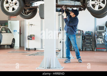 Mechanic fixing a lifted car - Stock Photo