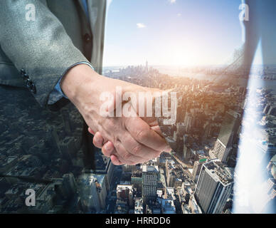 Double exposure of a business people shaking their hands in front of a big city - Stock Photo