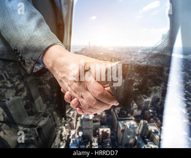 Business people shaking their hands. Double exposure effect - Stock Photo