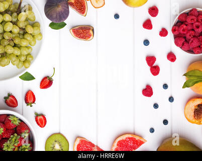 Variety of fruits and berries on the white wooden table, top view - Stock Photo