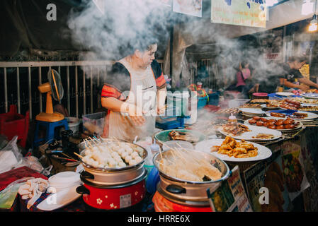 Chiang Mai, Thailand - August 27, 2016:  Thai woman cooks food for sale at the Saturday Night Market on August 27, - Stock Photo