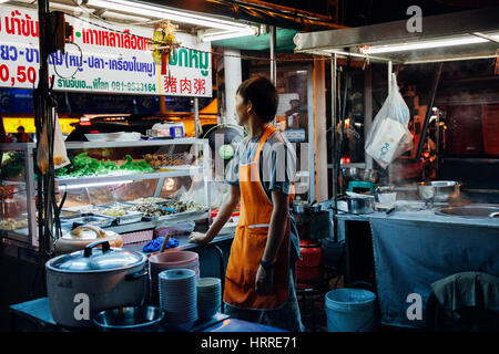 Chiang Mai, Thailand - August 27, 2016:  Food vendor waits for customers at the Saturday Night Market on August - Stock Photo