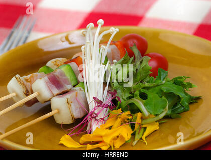 Bar-B-Q or BBQ of pork belly served with cherry tomato, onion, salad on skewers over brown plate. - Stock Photo