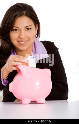 Beautiful business woman putting some money for her savings - isolated over a white background - Stock Photo