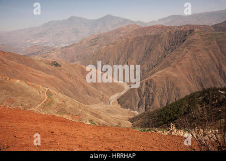 Small road placed between mountains of brown sand and dirt to travel from one side of the mountain to the other - Stock Photo