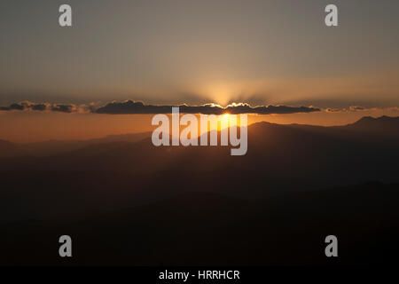 Sun setting behind the clouds and a silhouette of mountains at nightfall in China. - Stock Photo