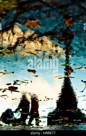 Silhouettes of walking people reflected in the water during rainy day in the city - Stock Photo