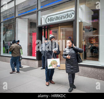 Shoppers leave Nintendo World with their Nintendo Switch consoles in Rockefeller Center in New York on the launch - Stock Photo