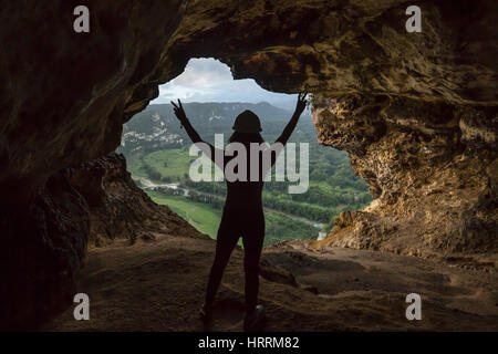 YOUNG WOMAN STANDS RAISING ARMS IN VICTORY CAVE WINDOW OVERLOOKING RIO GRANDE DE ARECIBO VALLEY PUERTO RICO - Stock Photo