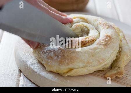 Female hands cutting freshly baked cheese pie on the wooden plate - Stock Photo