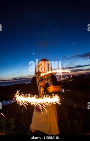 A woman holding sparklers at dusk celebrating the 4th of July at Birch Bay, Washington, USA. - Stock Photo