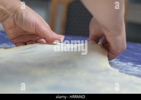Creating homemade Phyllo or strudel dough on a home table cloth for cheese pie or other kind of traditional pastry. - Stock Photo