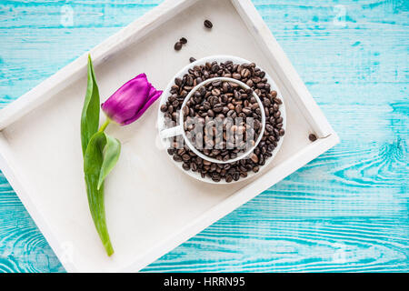 Vintage wooden tray with porcelain cup full of coffee beans and pink flowers on shabby chic mint background, top - Stock Photo
