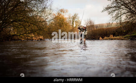Fly fisherman wading into the river, fly fishing for trout - Stock Photo