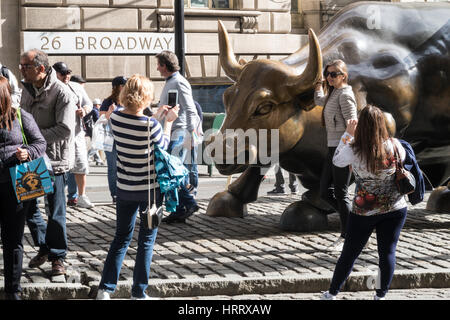 Tourists at Charging Bull Sculpture at Bowling Green Park, NYC - Stock Photo
