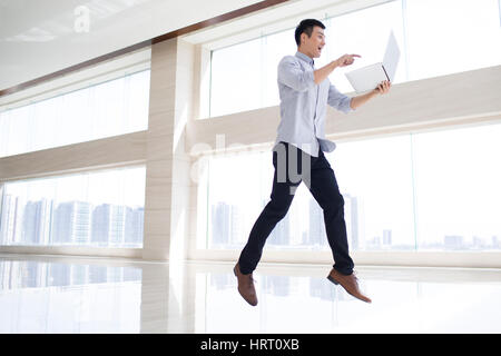 Cheerful businessman jumping with laptop in office building - Stock Photo