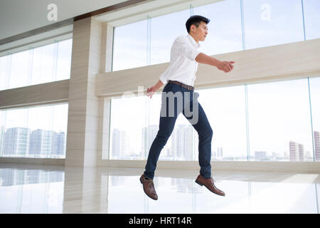 Young businessman jumping in office building - Stock Photo