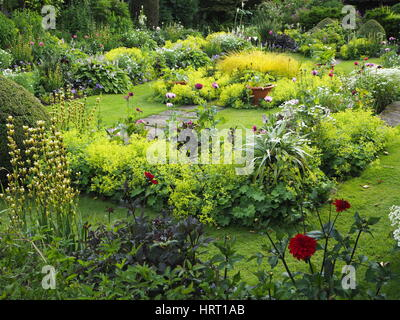 Chenies Manor Sunken garden in summertime with dahlias and lush green foliage plants around the ornamental pond - Stock Photo