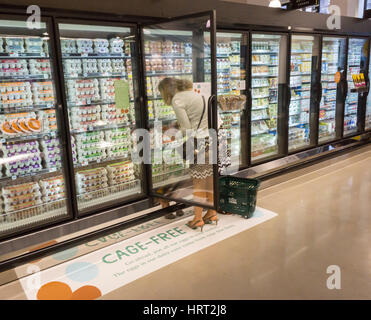 A shopper chooses cafe-free eggs in a cooler in the new Whole Foods Market in Newark, NJ on opening day Wednesday, - Stock Photo