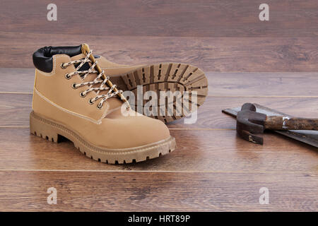 Work boots on wooden floor with tools - Stock Photo