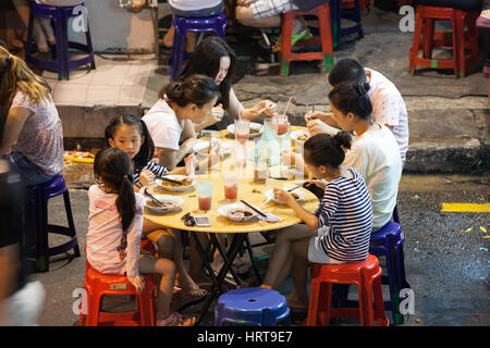 Georgetown, Malaysia - 03 August, 2014: Malaysian family dining at the street food stalls on Lebuh Chulia in historic - Stock Photo