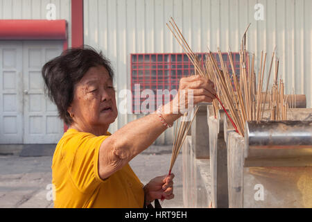 Georgetown, Malaysia - 02 August, 2014: Old woman burns incense in Kuan Yin Temple, one of the oldest Chinese temples - Stock Photo