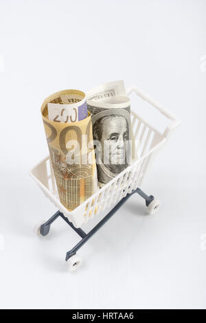 US100 Dollar and 200 Euro banknotes in shopping cart / trolley. Metaphor for exchange rates, free trade, trade war, - Stock Photo
