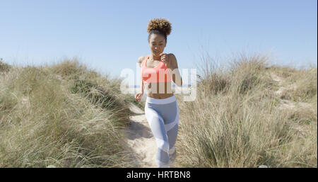 Horizontal outdoors shot of young woman jogging on Tarifa beach in lovely sunny day in Cadiz, Spain. - Stock Photo