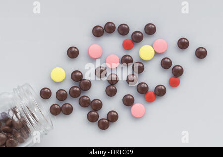 Different pills spill out of a glass jar on a light surface - Stock Photo