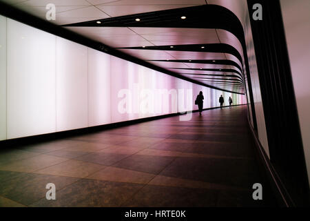 People walking through futuristic looking pedestrian tunnel featuring an LED integrated light wall in Granary Square - Stock Photo