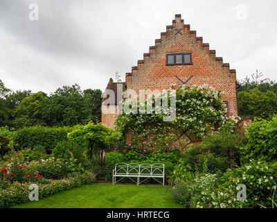 Chenies Manor pavilion with white climbing rose and summer border plants. A garden seat on the lawn by the tearoom, - Stock Photo