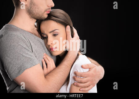 portrait of man hugging upset woman on black - Stock Photo