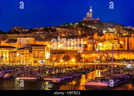 The harbor of Marseille at night. Looking towards the Cathedral de Notre-Dame-de-la-Garde high on a hill overlooking - Stock Photo