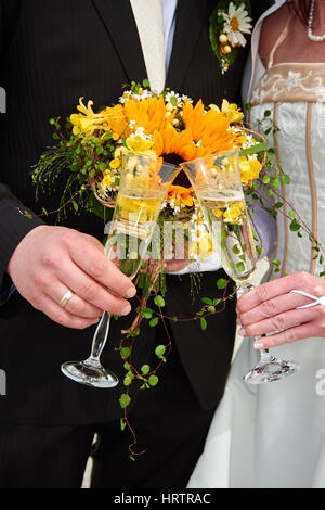 clink glasses by bride and groom - Stock Photo