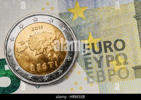 a 2 euro coin from Estonia on a 5 euro banknote - Stock Photo