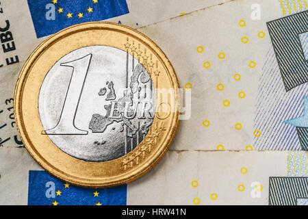 a 1 euro coin on euro banknotes - Stock Photo