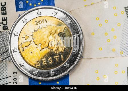 a 2 euro coin from Estonia on euro banknotes - Stock Photo