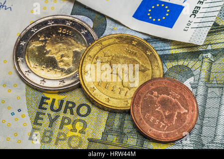 On a 5 euro banknote are three euro coins of the Baltic State Estonia - Stock Photo